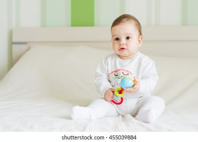 Baby girl sitting on the bed and playing with rattle