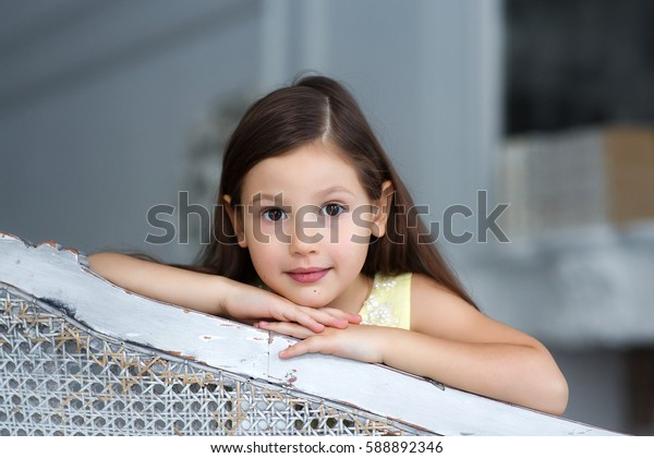 Baby girl sitting on the couch, cute black-haired toddler