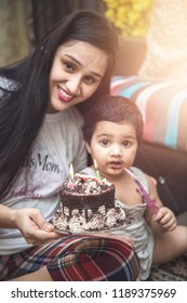 Baby girl sitting on the floor with mother holding birthday cake, Looking at camera.