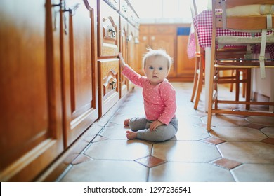 Baby girl sitting on the floor in the kitchen. Little child crawling at home and exploring things around her