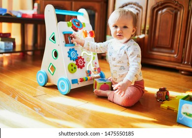 Baby girl sitting on the floor in nursery and playing with wooden push toy. Adorable toddler with baby-walker