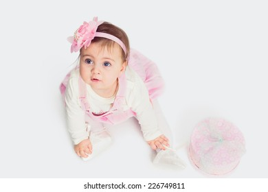 baby girl sitting on the floor with gift box  and looking up