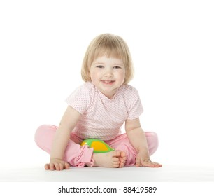 The baby girl is sitting on the floor with a toy