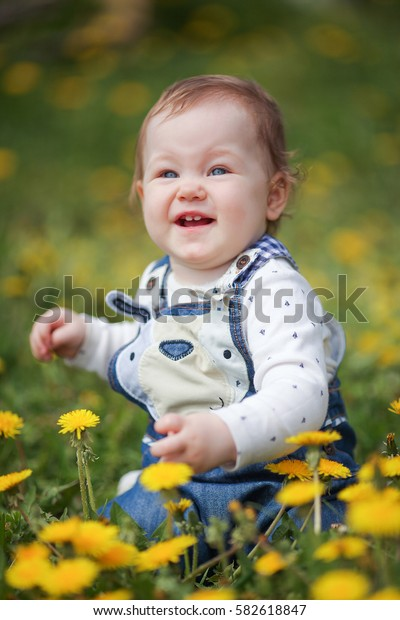 baby girl sitting on a glade of dandelions