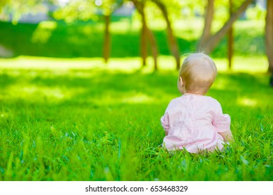 Baby girl sitting on green summer grass in back view and looking into the distance
