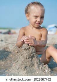Baby girl sitting on the sandy beach and playing near the sea. Summer vacations concept.