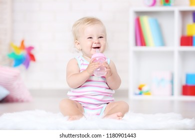 Baby girl sitting on white carpet with bottle