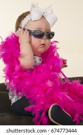 A baby girl sitting with a pink feathered boa, putting on her sunglasses showing off her style.