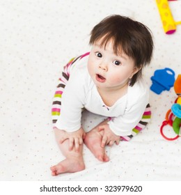 Baby girl sitting in playpen and looking up