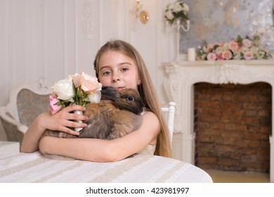 The baby girl is sitting at the table and hugs rabbit