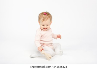 baby girl sitting with a wooden giraffe toy over white background in studio