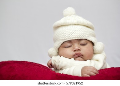 A Baby Girl Sleeping with off white Hat. Beautiful baby girl sleeping on the red blanket and wearing off white hat.