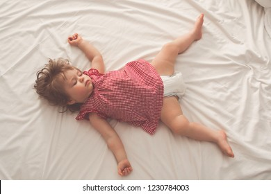 Baby girl sleeping on back with open arms and without pacifier in a bed with white sheets. Peaceful sleeping in a bright room. Pastel retro toned. Soft focus.