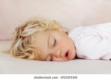 Baby girl sleeping on the bed under pink blanket. The girl has blonde curly hair.