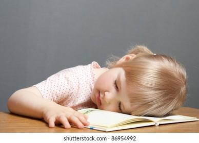 Baby girl is sleeping on the book. Grey background