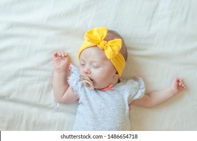 Baby girl sleeping on white bed