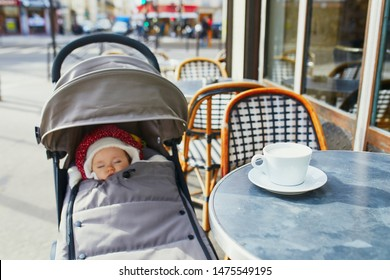 Baby girl sleeping in pram on outdoor terrace of Parisian street cafe with cup of hot coffee on the table. Going out with kids