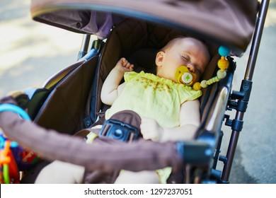 Baby girl sleeping in stroller. Little child in pram. Infant kid outdoors in pushchair