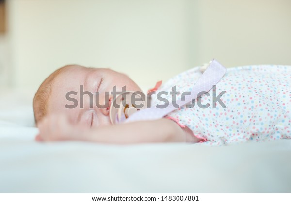 Baby girl sleeping in white bed with pacifier