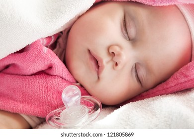 Baby girl sleeps in pink and white cotton towels with a pacifier nearby