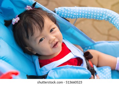 Baby girl smile sitting in stroller, childhood and people concept.