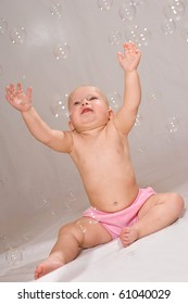 Baby girl with smiles at the bubbles floating around her