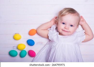 baby girl smiling portrait in beautiful white summer dress  easter eggs on blue white background