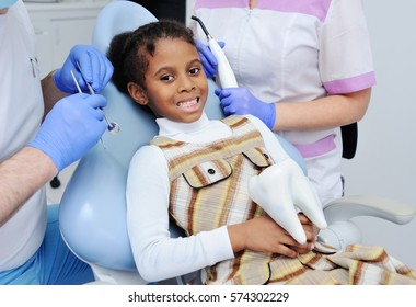 baby girl smiling and shows her white teeth in a dental chair