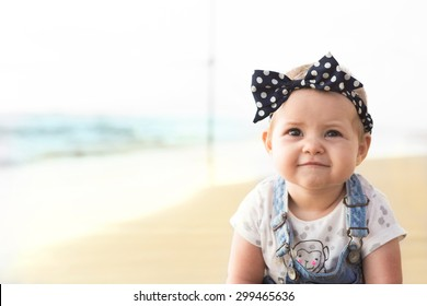 Baby girl is smiling and sitting on a beach near sea in jeans.