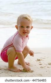 baby girl squatting down on a beach