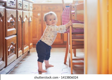 Baby girl standing on the floor in the kitchen and holding on to furniture. Little child oulling up at home
