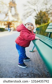 Baby girl standing on the street and holding on to bench. Little child pulling up outdoors. Happy kid in Paris near the Eiffel tower. Travelling with kids
