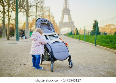 Baby girl standing on the street and holding on to pushchair. Little child pulling up outdoors. Happy kid in Paris near the Eiffel tower. Travelling with kids