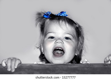 Baby girl stands in crib and giggles, garbles and makes all those cute baby noises.  Black and white with color added.