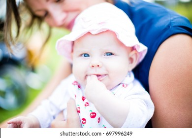 Baby girl sucking fingers held by mommy wearing sun hat