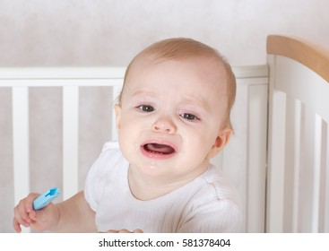 A baby girl suffers from gum pain. Closeup