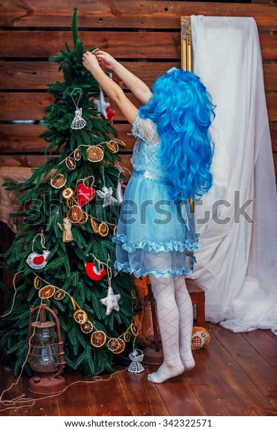 Baby girl in a suit Malvina dresses up Christmas tree