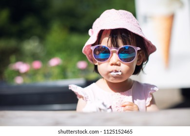 Baby girl with sunglass eating icecream