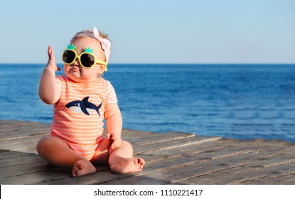 Baby girl in the sunglasses and orange striped shirt enjoying sun at the sea embankment. Child sitting on the ocean shore. Happy childhood and family vacation concept