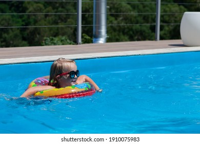 a baby girl swims in a pool with a lifebuoy