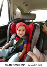 Baby girl toddler is sitting in a car in safety chair or baby car seat,