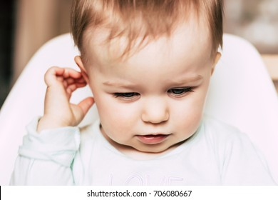 Baby girl touching her ear and looking down close-up. Family, baby, child, portrait, concentration, thinking, otolaryngology concept