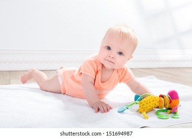 baby girl  with toy in the hand, lying on the floor
