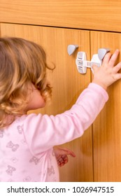 Baby girl trying to open the kitchen cabinet – baby proofing the door