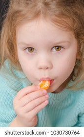 baby girl vegetarian eating a mandarin slice