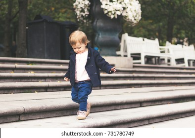 Baby girl walking on stairs in the park in Stockholm, Sweden. Autumn, baby, toddler, baby fashion concept