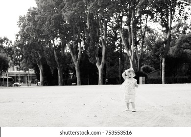 Baby girl walking in park. Natural summer emotional black and white portrait