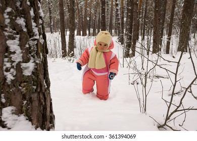 Baby girl walking in the winter forest