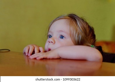 Baby girl watching movie hiding behind table. Toddler girl peeping over table.