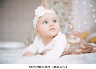 Baby girl wearing cute dress and headband, lies on a white cover in festively decorated room. With surprise watches in the camera, on a background a set of bright fires, soft focus. Warm beige and gol